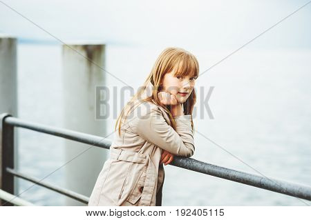 Outdoor portrait of adorable 9 -10 year old kid girl wearing modern beige trench coat, posing in a port on a cold day