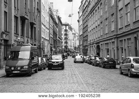People And Cars On Street In Old Riga Town