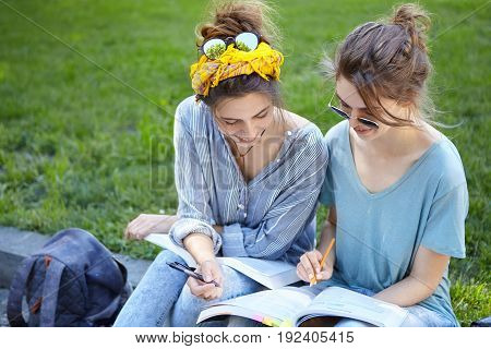 Two Female Students Sitting At Bench At College Campus Looking Attentively In Book Writing Something