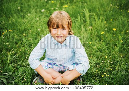 Outdoor portrait of adorable 6 year old boy wearing blue shirt sitting on the grass top view