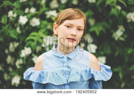 Adorable little kid girl playing in spring garden wearing light blue shirt summer fashion for children