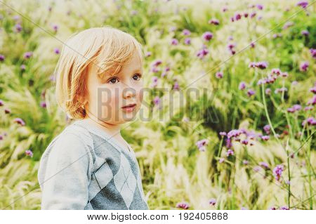 Adorable blond toddler boy playing in a garden wearing grey pullover