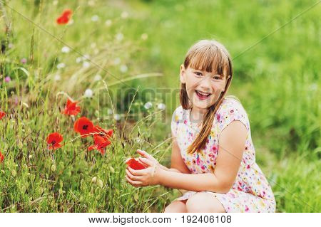 Outdoor portrait of adorable little blond girl playing with poppy flowers