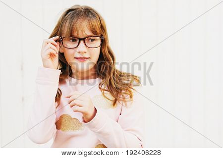 Outdoor portrait of a cute little 9 year old girl wearing soft pink sweatshirt and glasses
