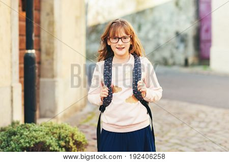 Outdoor portrait of a cute little 9 year old girl wearing soft pink sweatshirt dark backpack and glasses