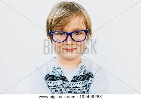 Close up portrait of adorable little kid boy wearing eyeglasses and grey sweatshirt