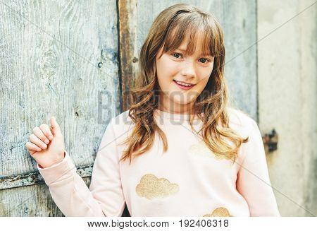 Fashionable little girl posing outdoors wearing light pink sweatshirt
