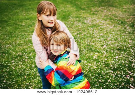 Spring portrait of adorable siblings little boy and girl playing together outside