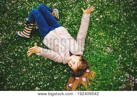 Funny little girl lying on bright green grass playing with soft flower petals in spring park wearing jacket and rain boots seasonal fashion for kids