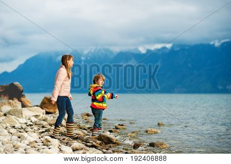 Two happy kids little brother and big sister playing together by lake Geneva on a very cloudy day with swiss mountains Alps on background. Image taken in Lausanne Switzerland