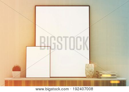 Front view of two vertical framed posters of different sizes standing on a wooden dresser in a room with gray walls. 3d rendering mock up toned image
