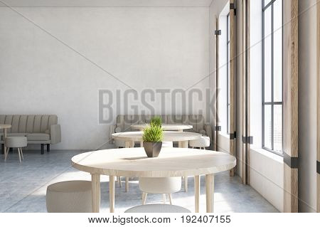 Modern cafe interior with concrete walls wooden floor round tables and chairs and beige sofas near tall windows. 3d rendering mock up