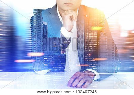 Close up of an unrecognizable young businessman sitting at his table against a night city panorama. Toned image double exposure