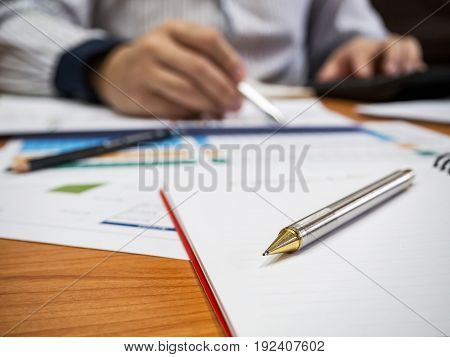 Close Up Of Pencil On Notebook With Businessman Background