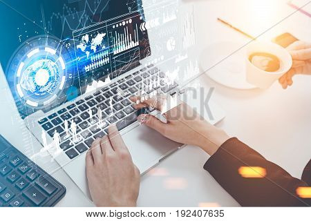 Close up of hands of an unrecognizable businesswoman. She is typing at her laptop keyboard. Graphs and holograms in the air. Toned image double exposure.