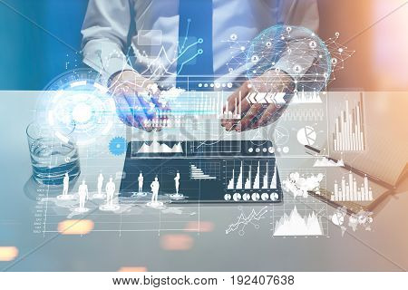 Front view of an unrecognizable businessman. He is at his workplace with a laptop lying on the desk. Graphs and holograms. Toned image double exposure.