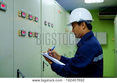 Engineer checking and monitoring the electrical system in the control room, industrial concept