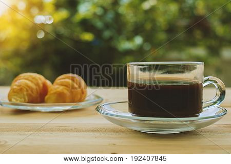 A cup of coffee and croissants on blurred green natural background, selective focus and vintage retro color