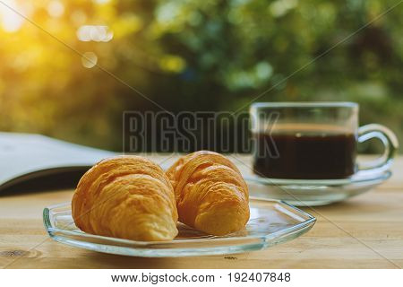 Croissants a cup of coffee and opened book on blurred green natural background, selective focus and vintage retro color