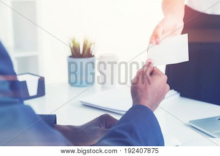 Close up of an unrecognizable young woman giving her business card to an African American businessman sitting with his back to the camera. Concept of business contacts. Mock up