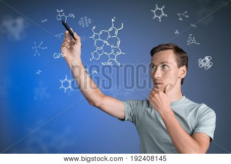 Man scientist with stylus or pen working with chemical formulas on blue background.
