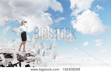 Portrait of a blond businesswoman standing on a giant rock with binoculars and looking at a city around her. There are papers flying around. Mock up