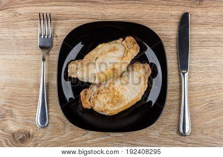 Fried Pork Cutlets In Black Plate, Fork And Knife