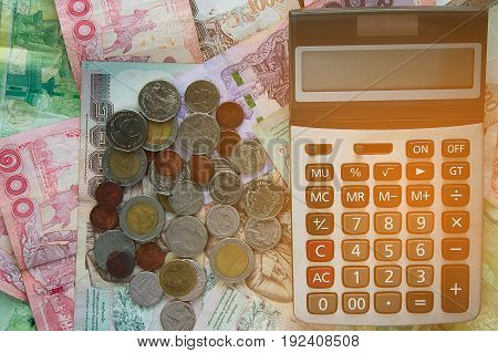 Calculator on Thai baht money banknotes and coins, business and finance concept