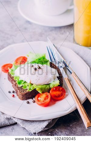 Rye Bread Toast and Poached Egg with Green Salad Cherry tomato cup of coffee and Orange Juice on the Wooden Table Background. Healthy Breakfast content