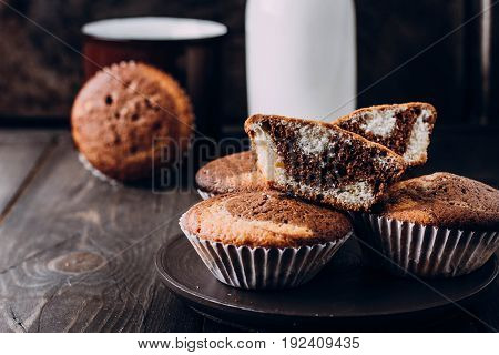 Homemade sweet chocolate vanilla muffins from two types of dough with bottle of milk on wooden table background. Copy space