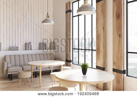 Corner of a modern cafe interior with concrete walls and floor wooden shutters at tall windows and round tables with chairs. 3d rendering mock up
