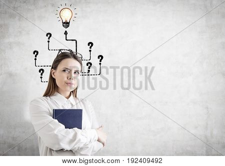 Portrait of an alert young woman with fair hair holding a blue book and standing with crossed arms near a concrete wall with many question marks and arrows. One is leading to a light bulb. Mock up