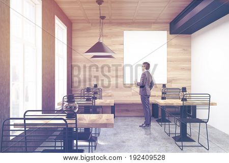 Man in a wooden and white wall cafe interior with old oil lamps on square wooden tables and a large vertical poster hanging on a gray wall. 3d rendering mock up toned image