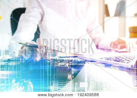 Close up of an unrecognizable businesswoman typing on a keyboard while sitting in an office. Blue cityscape and graphs. Toned image double exposure mock up.