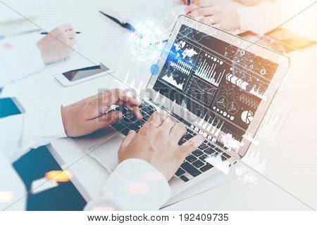 Close up of hands of an unrecognizable businessman. He is typing at his laptop keyboard. Graphs and holograms in the air. Toned image double exposure.