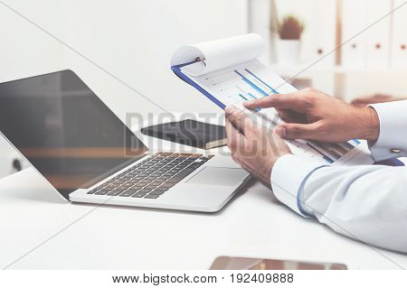 Close up of hands of an unrecognizable businessman holding a blue clipboard with graphs and statistics. Laptop on the table. Toned image