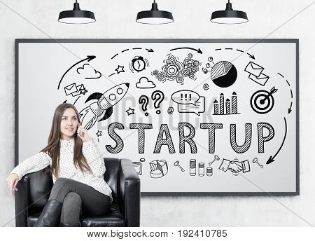 Young businesswoman with fair hair smiling and sitting in a leather armchair and talking on her smartphone. Whiteboard with a black start up sketch