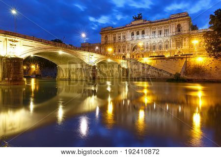 The Palace of Justice and bridge Ponte Umberto I with mirror reflection in Tiber River during morning blue hour in Rome, Italy