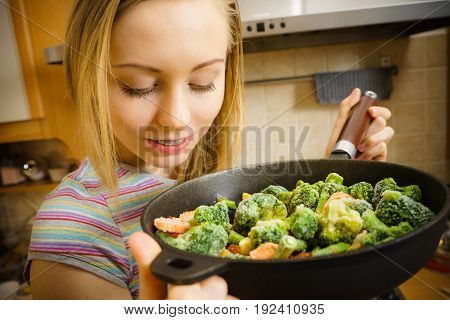 Woman Cooking Stir Fry Frozen Vegetable On Pan