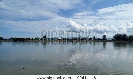 A calm watery lake, with bright clouds