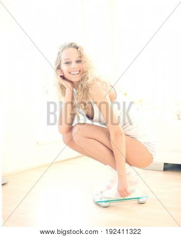 Portrait of happy woman crouching on weighing scale