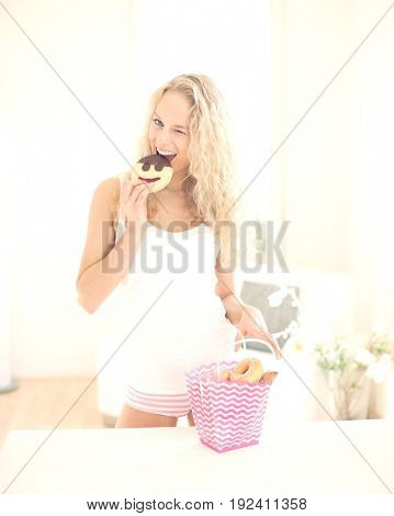 Portrait of happy woman eating cookie while winking at kitchen counter