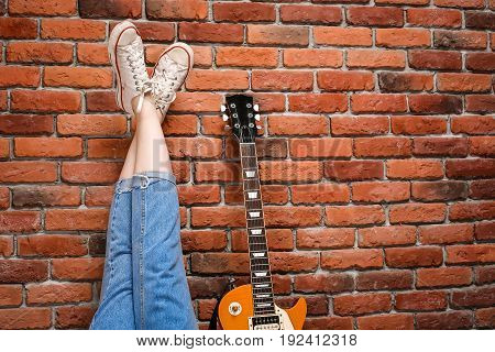 Close up of girl's legs and guitar over brick background. Copy space.