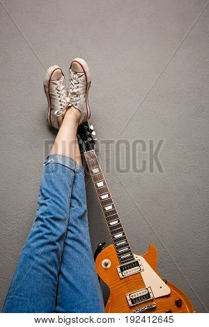 Close up of girl's legs and guitar over grey background. Copy space.