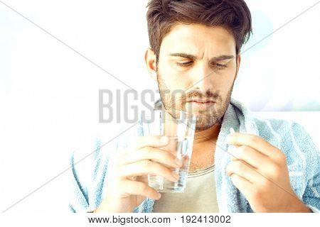 Sick man taking medicine in bedroom at home