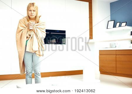 Portrait of young woman wrapped in blanket holding coffee mug in house