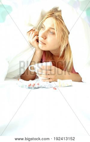 Young woman with coffee mug and medicines suffering from fever while covered in quilt on bed