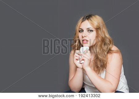 Studio shot of attractive long haired teenage girl holding her smart phone by both hands and looking at the camera. All is on the gray background. All potential trademarks and buttons are removed.