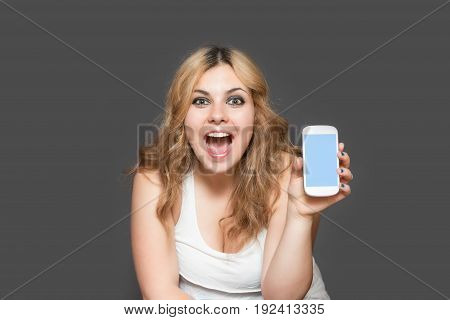 Attractive long haired teenage girl laughing with open mouth showing smart phone with blank touchscreen. All is on the gray background. All potential trademarks and buttons are removed.