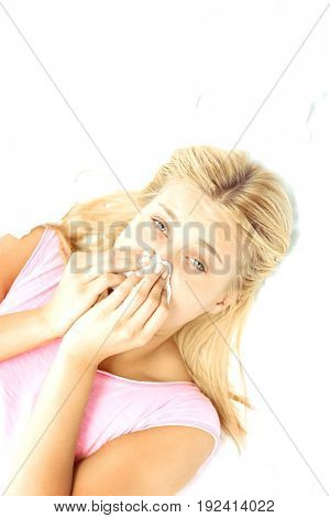 High angle portrait of young woman blowing nose in tissue paper while lying on bed
